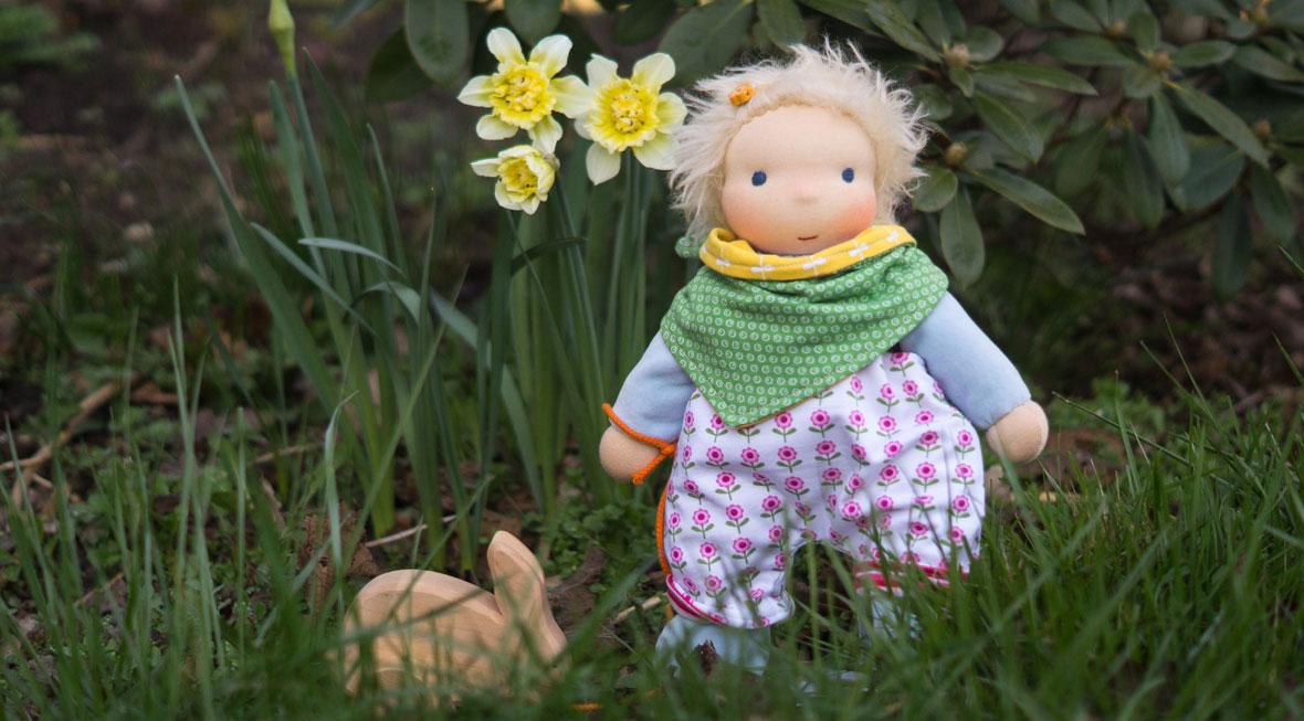 blondes Puppenkind Schmusepuppe mit Latzhose und Halstuch im Gras