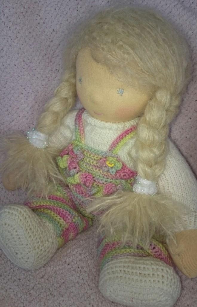 kleine Waldorfpuppe mit langen blonden Zöpfen und bunter Häkelose