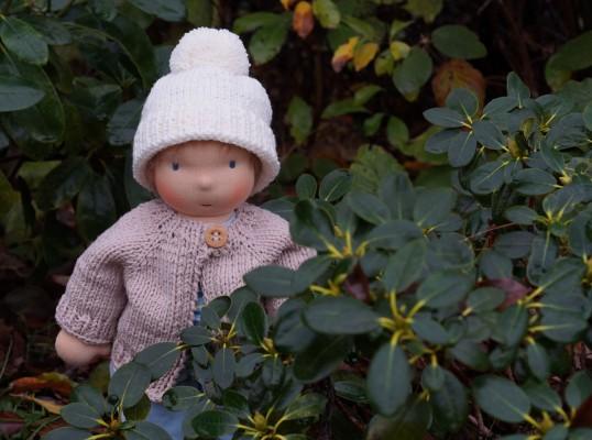 Puppenkind aus Stoff nach Waldorf Art schaut zwischen den Rododendronbüschen hervor. Es hat eine Strickjacke an und auf dem Kopf eine Bommelmütze.