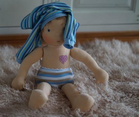 Puppenjunge hat sein Shirt lustig auf den Kopf gesetzt.