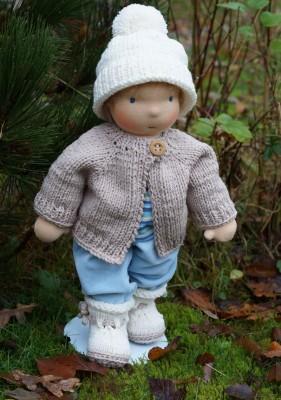 Puppenjunge nach Waldorfart bekleidet mit Nickihose, Strickjacke, Bommelmütze und Stiefelchen im herbstlichen Garten