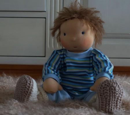 Stoffpuppe sitze auf einem Schaffell. Sie hat kurzes braunes Strubelhaar und blaue Augen, trägt ein Ringelshirt und eine hellblaue Nickihose, dazu weiße warme Stiefelchen