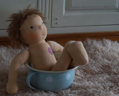 Stoffpuppe sitzt im Töpfchen wie in einer Badewanne und schaut frech heraus