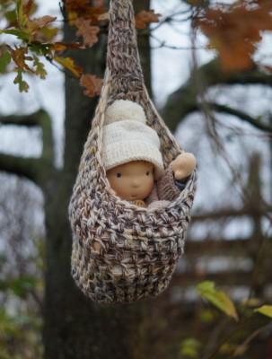 eine Waldorfpuppe hängt in einem gehäkelten Storchensäckchen in einem Eichenbaum. Er trägt eine weiße Bommelmütze.