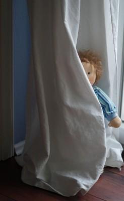 Puppenkind spielt Verstecken hinter einer Gardine, man sieht nur den Kopf und einen Arm