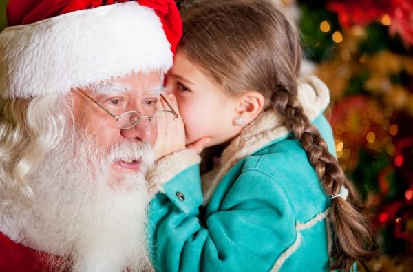 Mädchen flüstert den Weihnachtsmann etwas ins Ohr