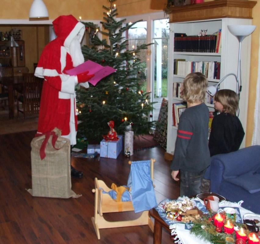 Weihnachtsmann steht vor 2 Kindern und liest aus seinem Buch vor