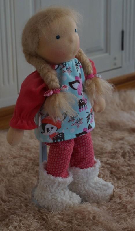 Waldorfpuppe mit langen blonden Zöpfen, bekleidet mit Tunika und Leggins