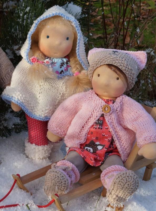 zwei Stoffpuppen nach Waldorfart bekleidet mit Strickjäcken und Stiefelchen darußen im Schnee