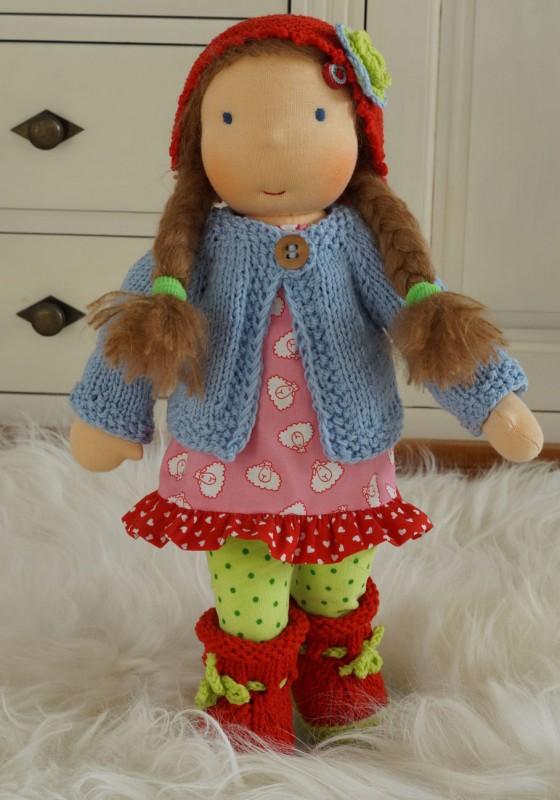 Puppe nach Waldorfart mit langen dunkelblonden Zöpfen, bekleidet mit rosa Kleidchen, grüner Leggins, hellblauer Strickjacke und roten Stiefelchen