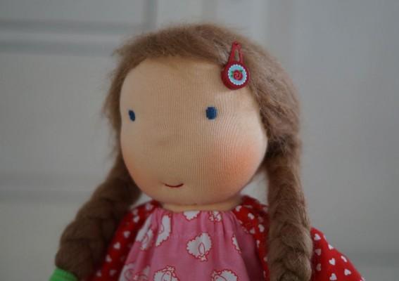 Gesicht einer Stoffpuppe mit blauen Augen und dunkelblonden Zöpfen