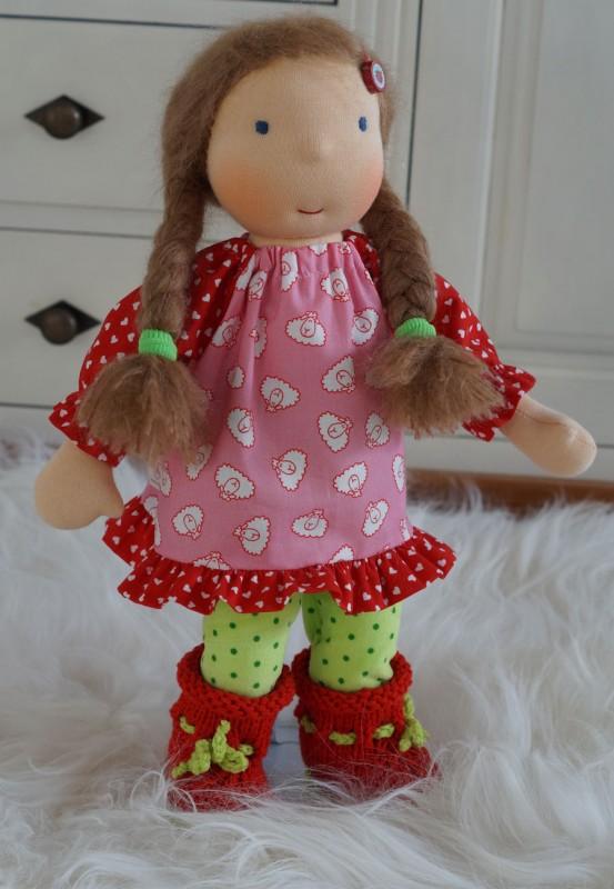 Waldorfpuppe mit dunkelblonden Zöpfen trägt ein rosa Kleid mit kleinen Schäfchen drauf, dazu eine hellgrüne Leggins mit Punkten und roten Strickstiefelchen