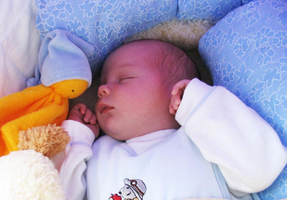 schlafendes Baby mit einer Schmusepuppe als Übergangsobjekt
