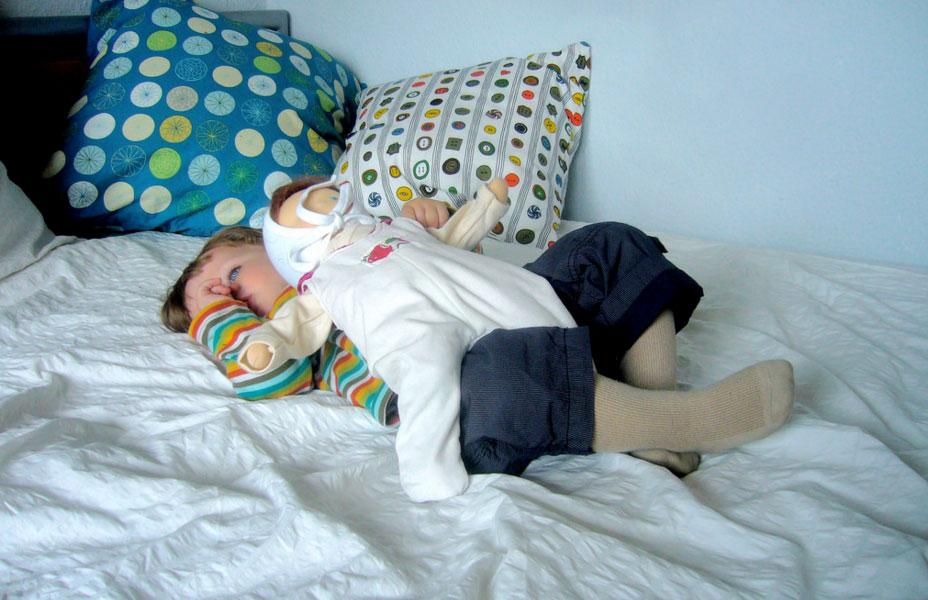 kleiner Junge kuschelt mit einer Babypuppe aus Stoff