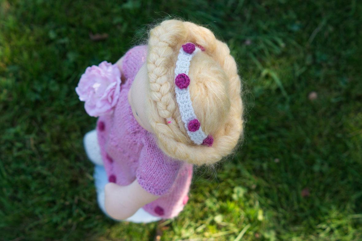 Puppe für Mädchen im Gras stehend, mit rosa Strickkleid und Rosenblüte in der Hand