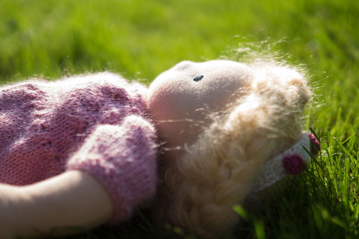 Stoffpuppe liegt im Gras, mit Röschenkleid - eine Puppe für Mädchen