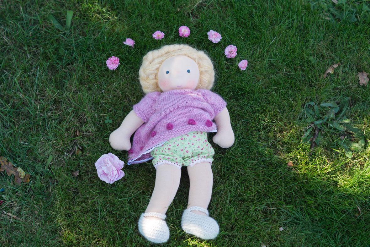 Puppe für Mädchen mit Strickkleid mit Röschen drauf und blonden geflochtenen Haaren