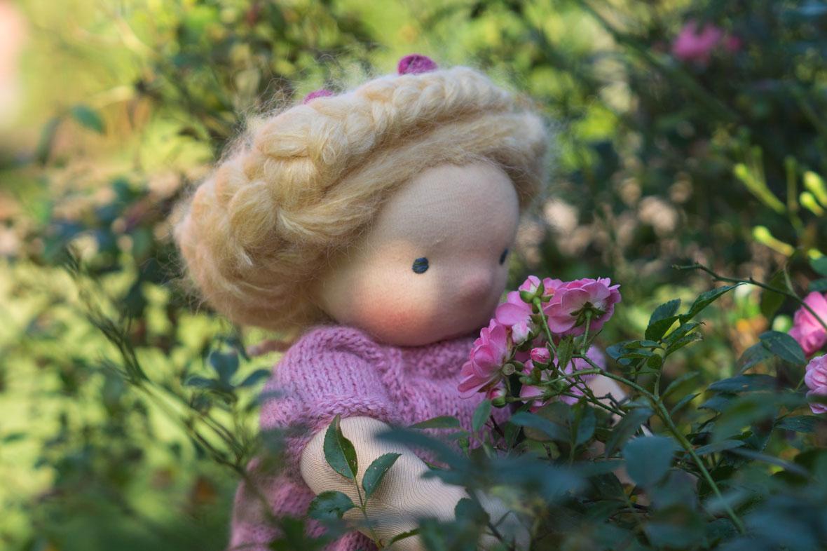 Stoff Puppe für Mädchen steht im Rosenbeet