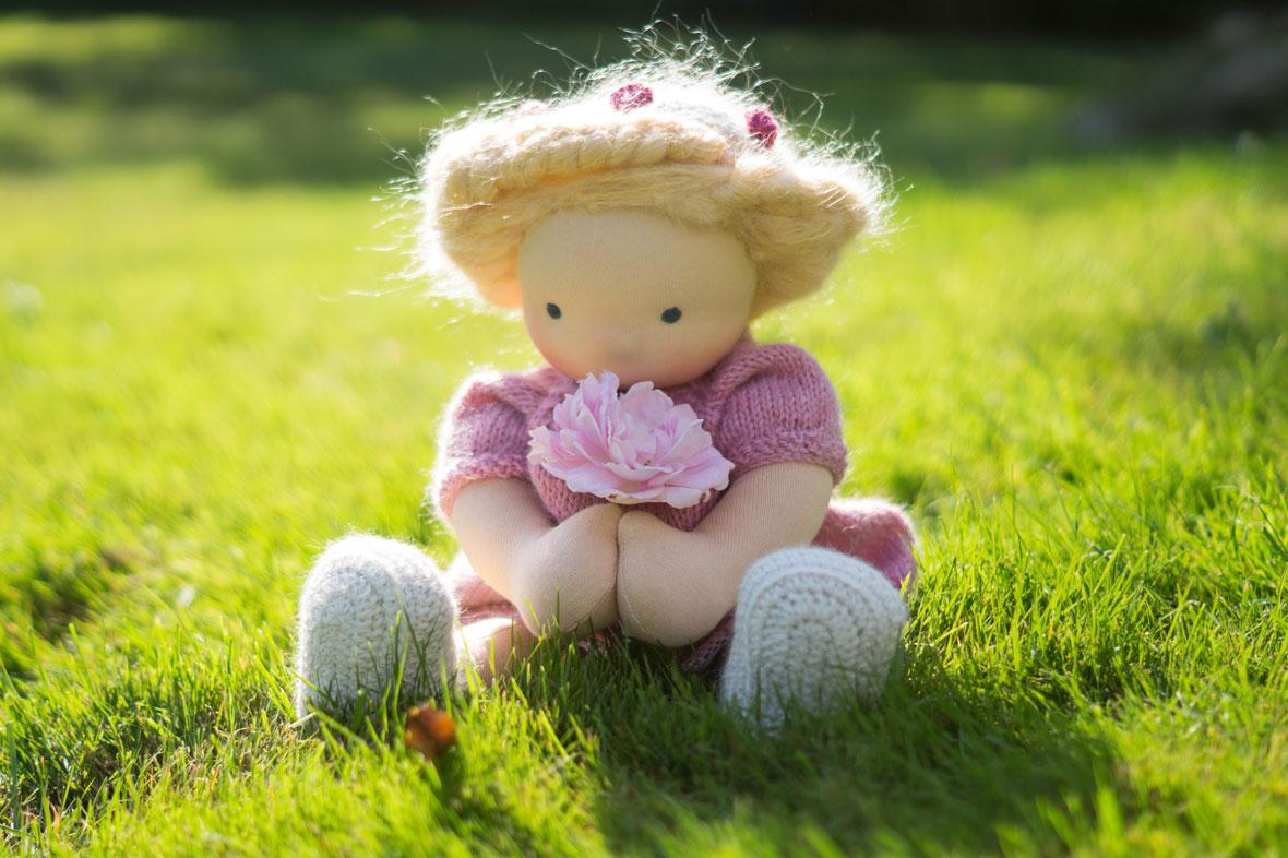 Puppe für Mädchen im Gras sitzend, mit rosa Strickkleid und Rosenblüte in der Hand