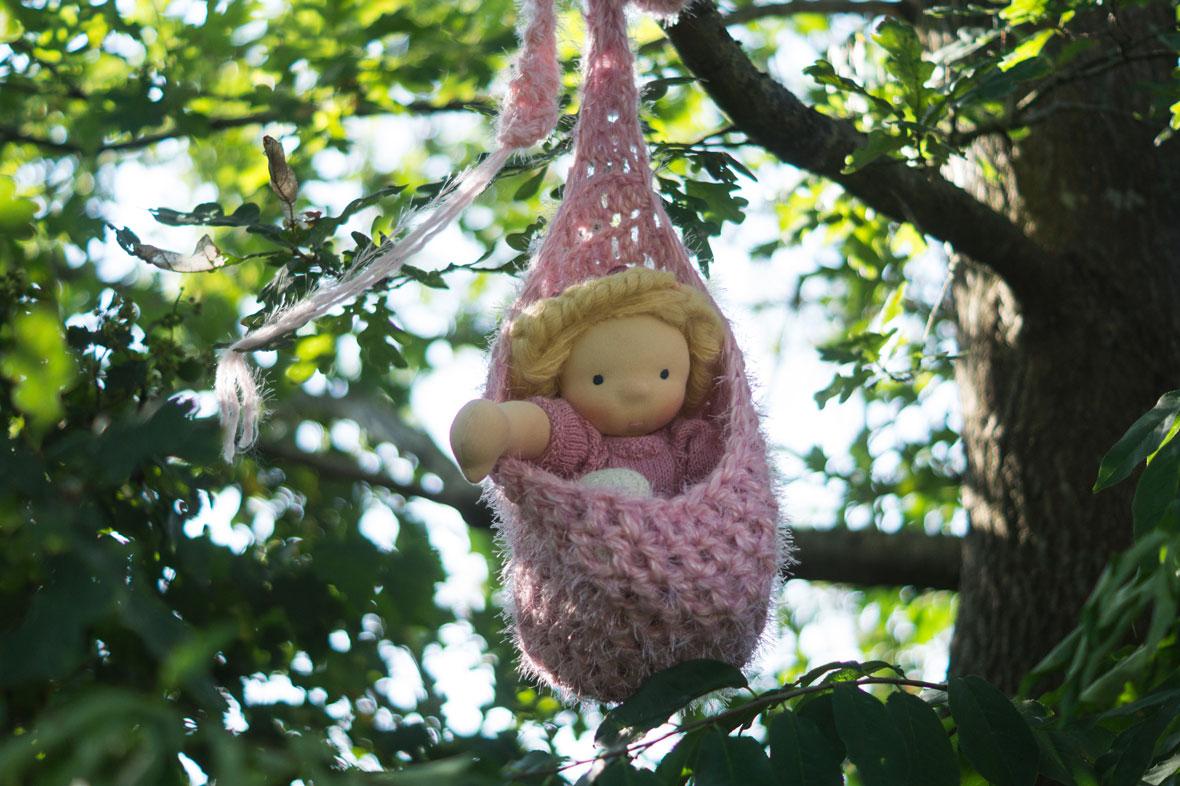 eine Puppe für Mädchen nach Waldorf Art in einem Häkelsäckchen am Baume hängend