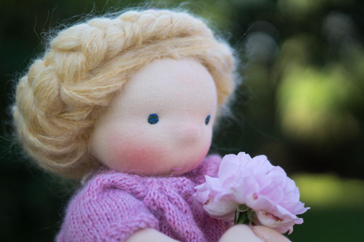 eine richtige Puppe für Mädchen mit blonden langen Haaren kunstvoll geflochten und Röschenhaarband