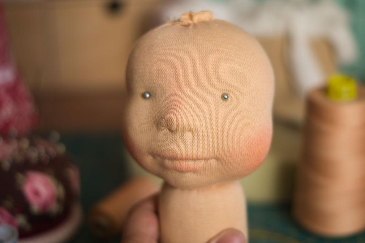 nadelgefilzter Puppenkopf mit Trikot und ersten Gesichtzügen