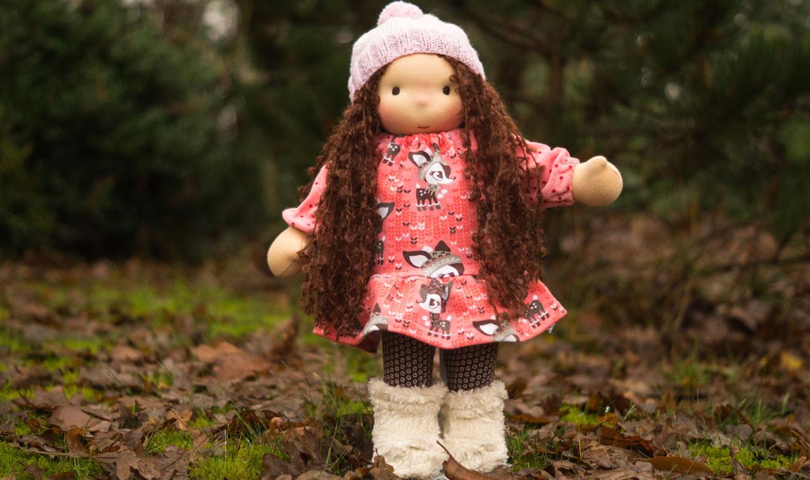 Waldorfpuppe mit langen Haaren, Bommelmütze, Kleid mit Kitzen und warmen Fellstiefeln steht im Garten. Ellis Puppen ab 3 Jahre