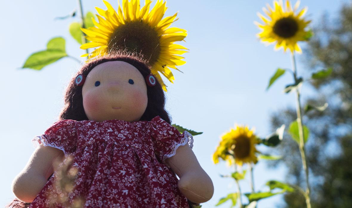 Walorfpuppe mit langen braunen Zöpfen steht iim Sonnenblumenfeld. Sie trägt ein langes rotes Baumwollkleid mit zarten Rüschen. Sie ist ein Herzenskind von Ellis Puppen ab 3 Jahre