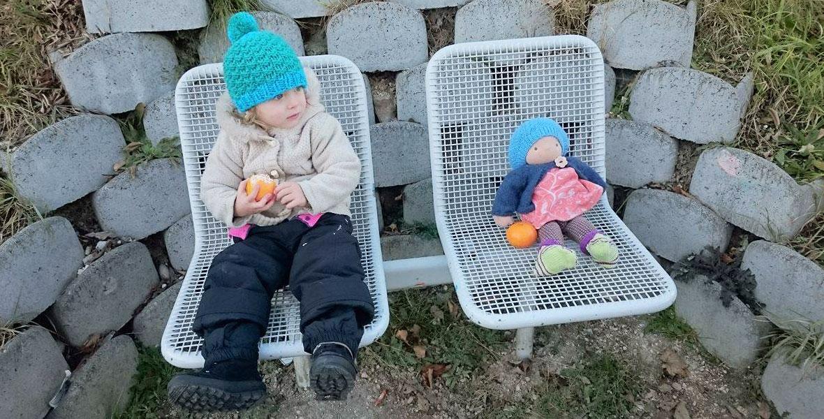 Kind isst zusammen mit seiner Waldorfpuppen eine Mandarine