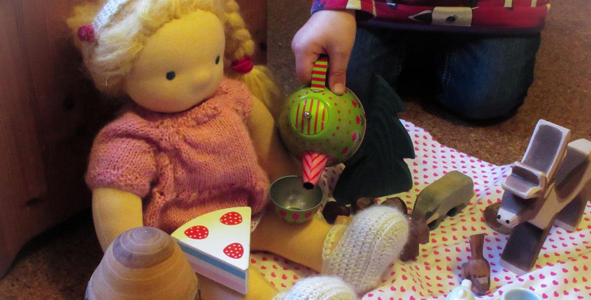 Waldorfpuppen Rollenspiel, Kind mit seiner Puppe beim Nachmittagstee