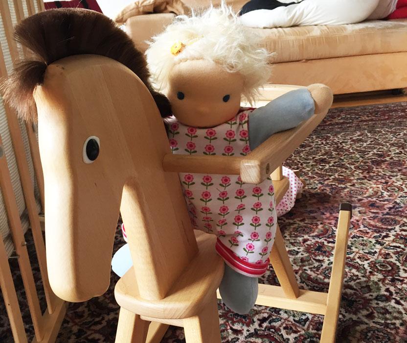 Puppenkind aus weichem Nicki reitet auf einem Schaujekpferd