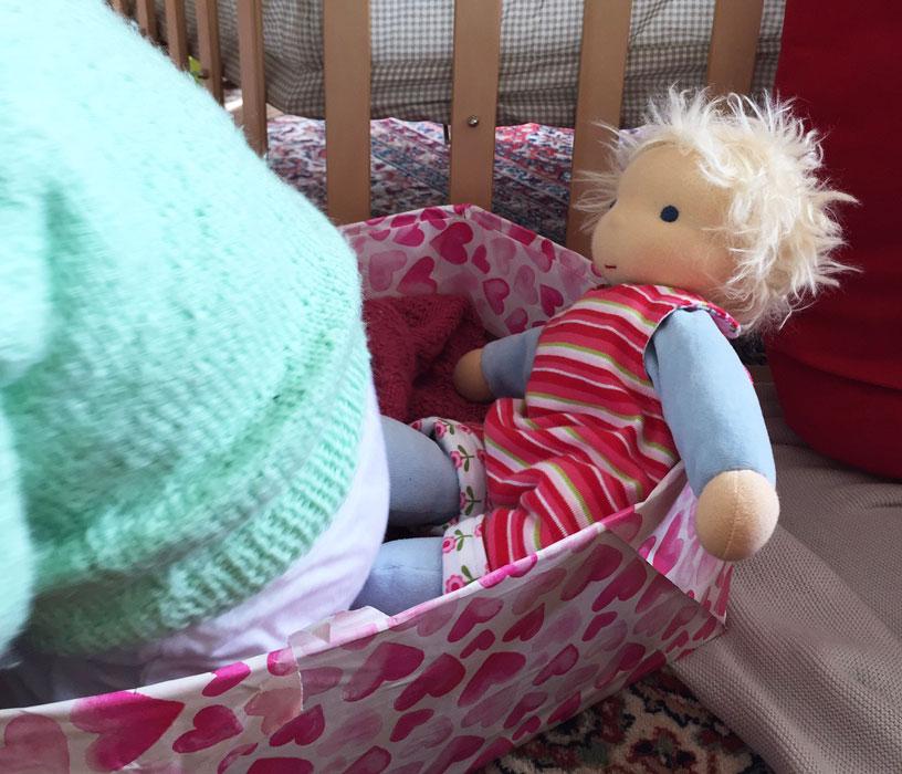 Puppenkind aus Stoff sitzt zusammen mit der Puppenmama im Puppenbett